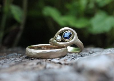Vielsesringe af guld med en mat hammerslået overflade. Damemodellen har en oval blå safir og hvid diamant hvor guldtråd snor sig rundt om.