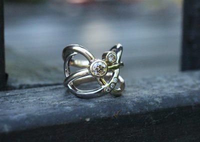 Bred ring lavet af flere tråde der krydser hinanden med en stor champagnefarvet diamant og flere små diamant i en af trådene.