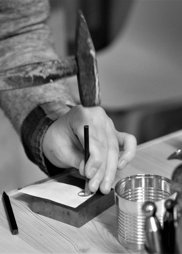 En person der står med en hammer og pundsel og banker mønster på en sølvplade.
