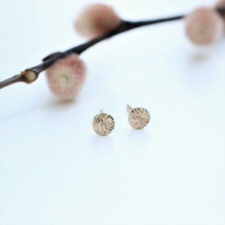 Runde ørestikkere i 14 karat guld med fræset overflade som ligner solens stråler.