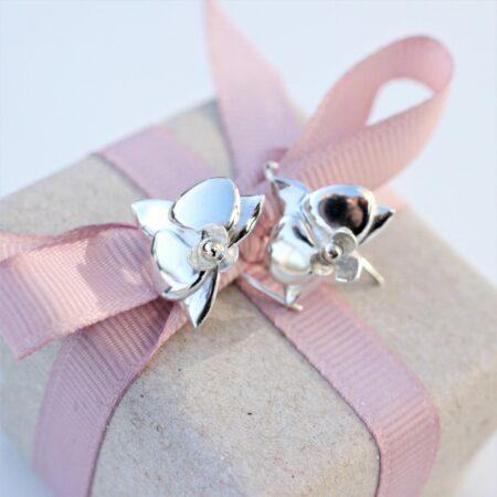 Øreringe der ligner orkide blomster i sølv som ligger oven på en indpakket gave.
