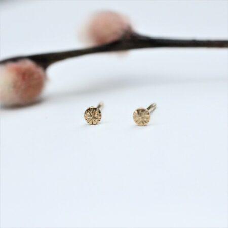 små runde ørestikkere i forgyldt sølv med fræset overflade, der ligner solens stråler.
