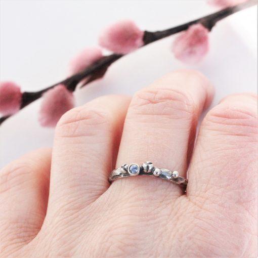 sølvring med sølvkugler og en blå safir på finger