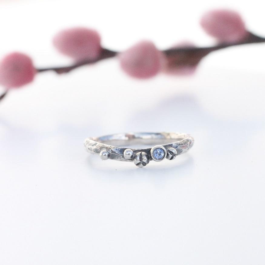 Sølv ring med grov overflade og sølvkugler, hvor der i den ene er en lyseblå safir