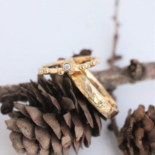 guld vielsesringe, hvor damemodel er tynd med kugler og herremodel bred og grov.
