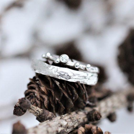 hvidgulds vielsesringe med diamant liggende på lærkegrene
