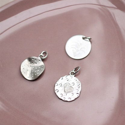 tre vedhæng i sølv, som er lavet på forskellige måder.