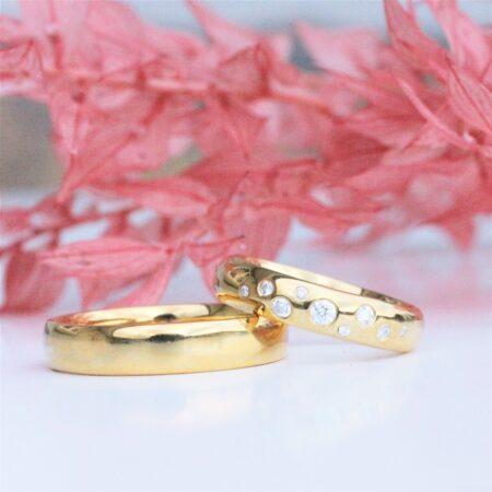 guld vielsesringe liggende oven på hinanden, blanke, hvor den ene er fyldt med diamanter.