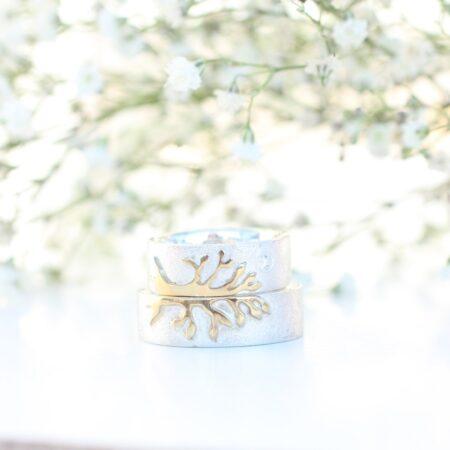 Vielsesringe i hvidguld, hvor der er et halvt træ af guld på hver ring.