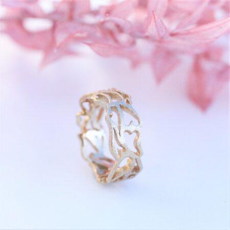 Guldring med udsavede hjerte stående på hvidt underlag og lyserøde blomster i baggrunden