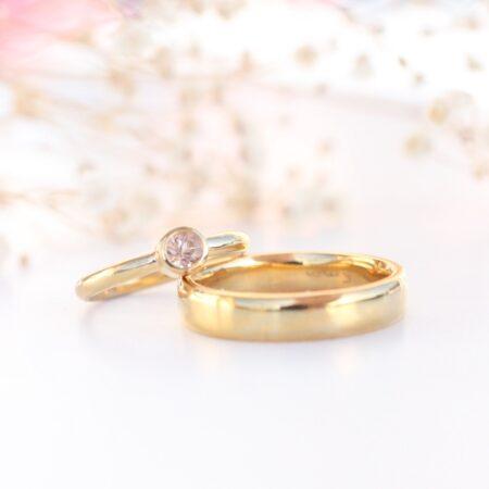 Klassiske vielsesringe i guld med et tvist af lyserød morganit i damemodel