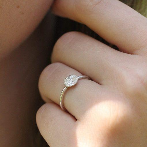 solstråle sølv ring på finger